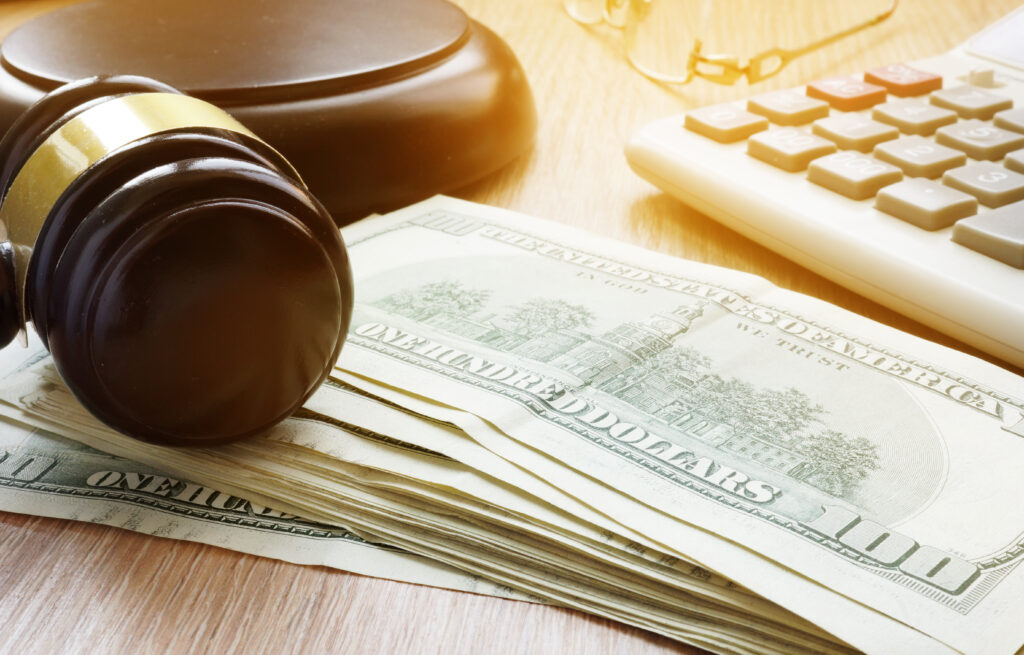 A judge's gavel near a stack of one-hundred dollar bills, representing the court system, justice, and how bail bonds work.